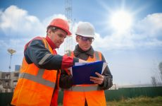 An engineer with a hard hat and helmet discussing a project at a construction site with a team leader. architecture construction concept. Industrial safety